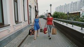 Οι ευτυχείς νέοι φίλοι γυναικών που περπατούν με τις τσάντες αγορών, ομιλία συζητούν την κατοχή της διασκέδασης αργός πυροβολισμό φιλμ μικρού μήκους