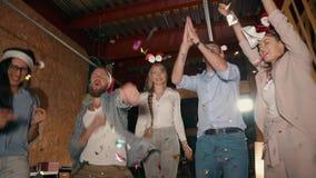 Οι ευτυχείς νέοι χορεύουν και ρίχνουν tinsel στο κόμμα νύχτας Χριστουγέννων απόθεμα βίντεο