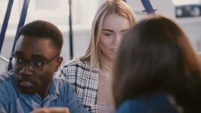 Οι ευτυχείς νέοι multiethnic επιχειρηματίες, άνδρας και γυναίκα, συνεργάζον απόθεμα βίντεο