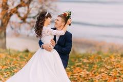 Οι ευτυχείς νεολαίες η νυφική τοποθέτηση ζευγών στο σύνολο φθινοπώρου lakeshore των πορτοκαλιών φύλλων Στοκ εικόνες με δικαίωμα ελεύθερης χρήσης