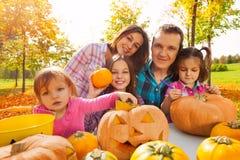 Οι ευτυχείς οικογενειακές χαράζοντας κολοκύθες προετοιμάζονται σε αποκριές Στοκ φωτογραφία με δικαίωμα ελεύθερης χρήσης
