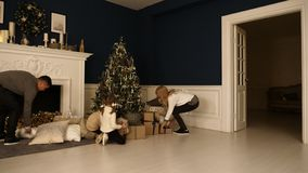Οι ευτυχείς οικογενειακοί περίπατοι στο καθιστικό για να ελέγξουν παρουσιάζουν κάτω από το χριστουγεννιάτικο δέντρο στοκ φωτογραφία με δικαίωμα ελεύθερης χρήσης