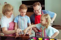 Οι ευτυχείς παππούδες και γιαγιάδες έχουν τη διασκέδαση με τα εγγόνια τους που προετοιμάζουν το γ Στοκ εικόνες με δικαίωμα ελεύθερης χρήσης