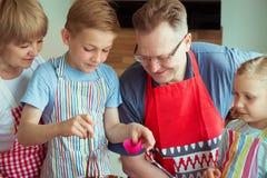 Οι ευτυχείς παππούδες και γιαγιάδες έχουν τη διασκέδαση με τα εγγόνια τους που προετοιμάζουν το γ Στοκ φωτογραφίες με δικαίωμα ελεύθερης χρήσης