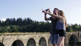 Οι ευτυχείς ρομαντικοί τουρίστες ζευγών μπροστά από την παλαιά γέφυρα κάνουν τη φωτογραφία απόθεμα βίντεο