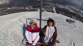 Οι ευτυχείς σκιέρ ανεβαίνουν στον ανελκυστήρα στο βουνό στην ηλιόλουστη ημέρα απόθεμα βίντεο