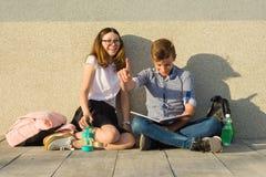 Οι ευτυχείς σπουδαστές στη διάβαση πανεπιστημιουπόλεων, έφηβοι κάθονται στον γκρίζο τοίχο, διαβάζουν τα εγχειρίδια, πίνουν το νερ στοκ εικόνες