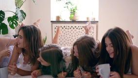 Οι ευτυχείς συγκινήσεις, φίλες στις πυτζάμες βρίσκονται στο κρεβάτι με τα φλυτζάνια του cappuccino και το γέλιο μαζί στο κόμμα κο φιλμ μικρού μήκους