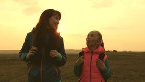 Οι ευτυχείς τουρίστες mom και η κόρη πηγαίνουν με τα σακίδια πλάτης στην πεδιάδα οικογένεια στα ταξίδια διακοπών έννοια της αθλητ απόθεμα βίντεο