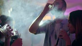Οι ευτυχείς φίλοι αυξάνουν τα γυαλιά για να κάνουν μια φρυγανιά με ένα ποτό στον καπνό hookah στη λέσχη απόθεμα βίντεο