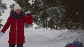 Οι ευτυχείς φίλοι κοριτσιών παίζουν τις χιονιές στο δασικό παιχνίδι παιδιών πεύκων με το χιόνι στο πάρκο zimy Διακοπές Χριστουγέν απόθεμα βίντεο