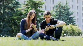 Οι ευτυχείς φίλοι χρησιμοποιούν τα τηλέφωνά τους χαλαρώνοντας σε ένα πάρκο πόλεων στη χλόη, να κουβεντιάσουν απόθεμα βίντεο