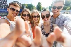 Οι ευτυχείς φίλοι που παίρνουν selfie και που παρουσιάζουν φυλλομετρούν επάνω Στοκ φωτογραφία με δικαίωμα ελεύθερης χρήσης