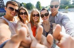 Οι ευτυχείς φίλοι που παίρνουν selfie και που παρουσιάζουν φυλλομετρούν επάνω Στοκ Φωτογραφίες