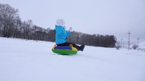 Οι ευτυχείς φωτογραφικές διαφάνειες νέων κοριτσιών γλιστρούν κάτω μέσα το χιόνι σε έναν διογκώσιμο σωλήνα και τα κύματα χιονιού τ απόθεμα βίντεο