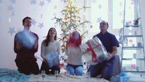 Οι ευτυχείς χαμογελώντας φίλοι ρίχνουν και πιάνουν τα δώρα κιβωτίων παρουσιάζει τη μύγα στα χέρια τους Οι εύθυμοι φίλοι γιορτάζου απόθεμα βίντεο