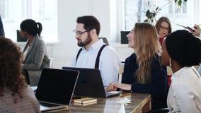 Οι ευτυχείς χαμογελώντας multiethnic διευθυντές γραφείων κάθονται στον πίνακα, γέλιο στον εταιρικό κύκλο μαθημάτων κατάρτισης στο απόθεμα βίντεο