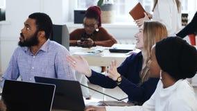 Οι ευτυχείς χαμογελώντας multiethnic επιχειρηματίες που κάθονται στο γραφείο παρουσιάζουν τη συνεδρίαση, που χτυπά χαρωπά σύγχρον απόθεμα βίντεο