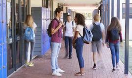 Οι εφηβικοί συμμαθητές στέκονται στο σχολικό διάδρομο στοκ εικόνα