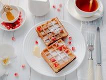 Οι εύγευστες βιενέζικες βάφλες στόμα-ποτίσματος με τους σπόρους μελιού και ροδιών σε ένα άσπρο πιάτο, ανάβουν το ξύλινο υπόβαθρο Στοκ εικόνες με δικαίωμα ελεύθερης χρήσης