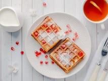 Οι εύγευστες βιενέζικες βάφλες στόμα-ποτίσματος με τους σπόρους μελιού και ροδιών σε ένα άσπρο πιάτο, ανάβουν το ξύλινο υπόβαθρο Στοκ Εικόνες