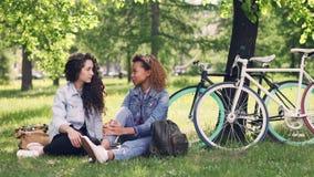 Οι εύθυμες νέες γυναίκες καυκάσιες και ο αφροαμερικάνος κουβεντιάζουν στο πάρκο στηργμένος μετά από να οδηγήσουν τα ποδήλατα σε ό απόθεμα βίντεο