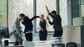 Οι εύθυμοι άνδρες και οι γυναίκες έχουν το κόμμα στο γραφείο που χορεύει με τα έγγραφα έπειτα που ρίχνει τους στον αέρα και το γέ φιλμ μικρού μήκους
