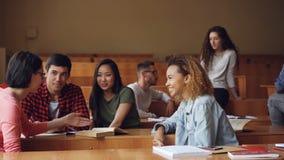 Οι εύθυμοι νεαροί άνδρες και οι γυναίκες χαλαρώνουν κατά τη διάρκεια του σπασίματος στο κολλέγιο, οι νέοι κουβεντιάζουν, γελούν κ απόθεμα βίντεο