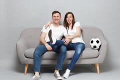 Οι εύθυμοι οπαδοί ποδοσφαίρου ανδρών γυναικών ζευγών στην άσπρη ευθυμία μπλουζών υποστηρίζουν επάνω την αγαπημένη ομάδα με τη σφα στοκ φωτογραφία
