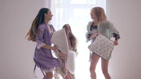 Οι εύθυμοι φίλοι γυναικών πηδούν και πάλη με τα μαξιλάρια στο κρεβάτι κατά τη διάρκεια του κόμματος πυτζαμών σε σε αργή κίνηση απόθεμα βίντεο