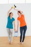 Οι εύθυμοι φίλοι με τις βούρτσες και το χρώμα μπορούν στο καινούργιο σπίτι Στοκ Φωτογραφία