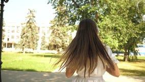 Οι εύθυμοι χοροί κοριτσιών πηγαίνουν στο πάρκο το καλοκαίρι την άνοιξη όμορφο κορίτσι που χορεύει, που κυματίζει το χέρι της και  φιλμ μικρού μήκους