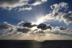 Οι ελαφριές ακτίνες λάμπουν μέσω της ομάδας σύννεφων Στοκ Εικόνες