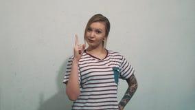 Οι ελκυστικές νεολαίες η γυναίκα στο ριγωτό πουκάμισο, έχουν την ιδέα και σηκώνουν το δάχτυλο απόθεμα βίντεο