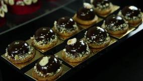 Οι ζαχαροπλάστες δίνουν τα τεθειμένα μικρά στρογγυλά επιδόρπια σοκολάτας απόθεμα βίντεο