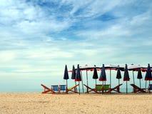 Οι ζωηρόχρωμες καρέκλες και οι ομπρέλες παραλιών για τον τουρισμό χαλαρώνουν στην κλίση Στοκ Φωτογραφία
