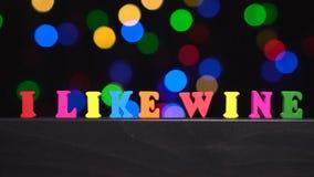 Οι ζωηρόχρωμες λέξεις ` που συμπαθώ το κρασί ` από τις πολύχρωμες ξύλινες επιστολές μπροστά από την περίληψη θόλωσαν το υπόβαθρο  απόθεμα βίντεο