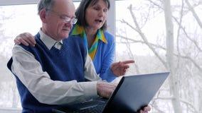 Οι ηλικιωμένες οικογενειακές σε απευθείας σύνδεση αγορές με το lap-top ξοδεύουν το χρόνο στο διαδίκτυο στις διακοπές στο σπίτι φιλμ μικρού μήκους