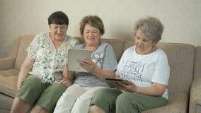 Οι ηλικιωμένες γυναίκες εξετάζουν τις φωτογραφίες στην οθόνη των ταμπλετών φιλμ μικρού μήκους