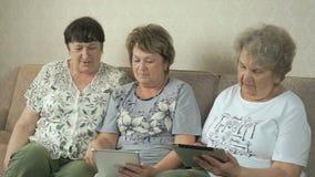 Οι ηλικιωμένες γυναίκες εξετάζουν τις φωτογραφίες χρησιμοποιώντας τις ψηφιακές ταμπλέτες απόθεμα βίντεο
