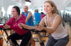 Οι ηλικιωμένοι κάνουν τον αθλητισμό στα ποδήλατα άσκησης στοκ εικόνες