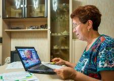 Οι ηλικιωμένοι μια χαμογελώντας γυναίκα χρησιμοποιούν το σύστημα ανοικτής γραμμής της τράπεζας για να πληρώσουν τους λογαριασμούς Στοκ Εικόνες