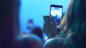 Οι θαυμαστές με το κύτταρο τηλεφωνούν στο βίντεο αρχείων συμφωνούν τη νύχτα παρουσιάζουν ότι επάνω το υπόβαθρο στο επίκεντρο φωτι απόθεμα βίντεο
