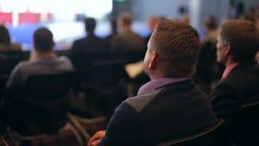 Οι θεατές εξετάζουν την οθόνη σε μια μεγάλη αίθουσα απόθεμα βίντεο