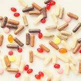 Οι θεραπευτικά κάψες και τα χάπια είναι διεσπαρμένες σε ένα φως Στοκ Εικόνες