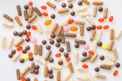 Οι θεραπευτικά κάψες και τα χάπια είναι διεσπαρμένες σε ένα φως Στοκ Φωτογραφίες