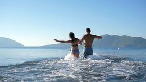 Οι θερινές διακοπές, εύθυμος άνδρας με τα χέρια εκμετάλλευσης γυναικών τρέχουν για να κολυμπήσουν εν πλω απόθεμα βίντεο