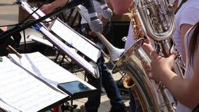 Οι θηλυκοί μουσικοί παίζουν saxophones στη δημοτική ορχήστρα αποδίδοντας στη συναυλία υπαίθρια απόθεμα βίντεο