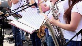 Οι θηλυκοί μουσικοί παίζουν saxophones στη δημοτική ορχήστρα αποδίδοντας στη συναυλία υπαίθρια φιλμ μικρού μήκους