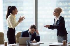 Οι θηλυκοί συνεργάτες έχουν τη διαφωνία πέρα από το έγγραφο στη συνεδρίαση στοκ εικόνα με δικαίωμα ελεύθερης χρήσης